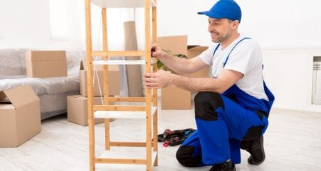Repairman Installing Wooden Shelf Wearing Blue Coverall Working Indoor
